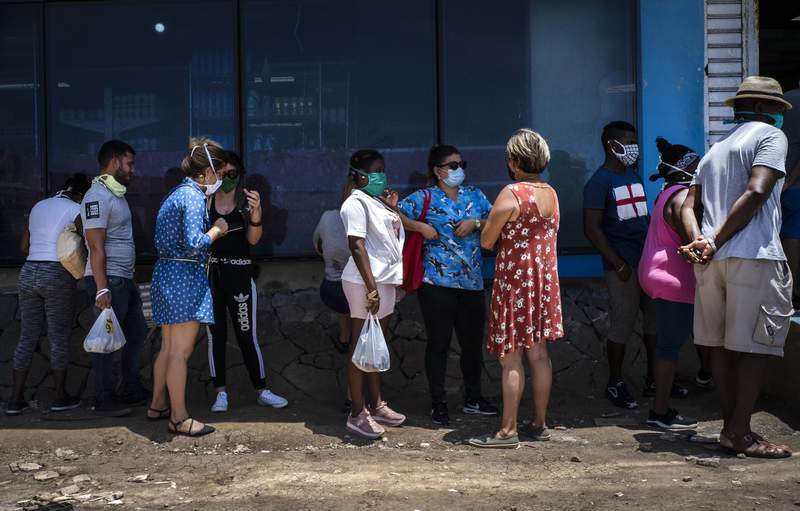 People wearing face masks amid the spread of the new coronavirus visit while waiting to enter a government-run food store in Havana, Cuba, Tuesday, May 19, 2020. State media has started a campaign of zero tolerance for anyone attempting to cash in on the fallout from the spread of the new coronavirus, like hoarding and speculative pricing, which has imposed even more distress on Cubans who were already used to shortages and long lines in their efforts to find basic necessities. (AP Photo/Ramon Espinosa)
