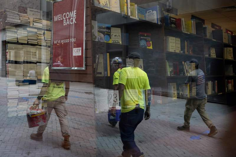 Workers are reflected in a window of a bookstore, Monday, Sept. 28, 2020, in the Harvard Square neighborhood of Cambridge, Mass. U.S. consumer confidence rebounded more quickly in September than most economists had expected, but it remains well below levels that preceded the pandemic. The Conference Board reported Tuesday, Sept. 29 that its consumer confidence index rose to a reading of 101.8, up from 86.3 in August. (AP Photo/Steven Senne)