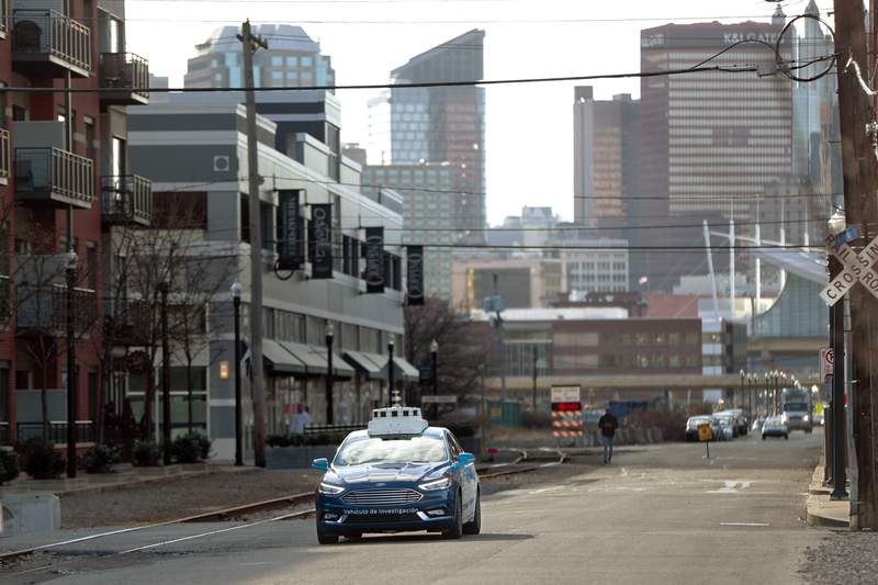 FILE - In this Dec. 18, 2018 file photo, one of the test vehicles from Argo AI, Ford's autonomous vehicle unit, navigates through the strip district near the company offices in Pittsburgh.  The U.S. governments road safety agency has set up an online map that will let people track where autonomous vehicles are being tested. The National Highway Traffic Safety Administration launched the tool Wednesday, Sept. 2, 2020, showing data about testing on public roads in 17 cities.  (AP Photo/Keith Srakocic, File)
