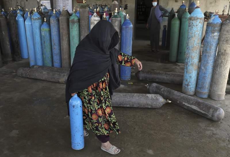 Una mujer carga un cilindro de oxgeno mdico el sbado 19 de junio de 2021 en una planta privada en Kabul, Afganistn. (AP Foto/Rahmat Gul)