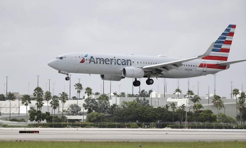FILE - An American Airlines Boeing 737-823 lands at Miami International Airport, Monday, July 27, 2020, in Miami.American Airlines said Tuesday, Aug. 25 that it will furlough or lay off 19,000 employees in October as it struggles with a sharp downturn in travel because of the pandemic. Flight attendants will bear the heaviest cuts, with 8,100 losing their jobs.  (AP Photo/Wilfredo Lee, File)
