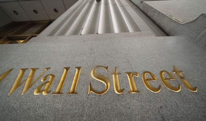 FILE - In this Nov. 5, 2020 file photo, a sign for Wall Street is carved in the side of a building, in New York.  Stocks are pushing higher in early trading on Wall Street, Friday, June 4, 2021, putting most major indexes back to gains for the week.  (AP Photo/Mark Lennihan, File)