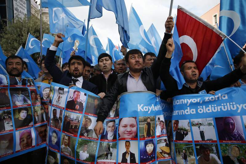 FILE - In this Tuesday, Nov. 6, 2018 file photo,  people from the Uighur community living in Turkey carrying East Turkestan flags, chant slogans during a protest in Istanbul,  against what they allege is oppression by the Chinese government to Muslim Uighurs in far-western Xinjiang province.  An independent tribunal in Britain aiming to establish whether the Chinese governments alleged rights abuses against Uighur Muslims in the far western Xinjiang region constitute genocide is expected to hear dozens of witness testimonies when it holds its first public hearing in London in May. Organizer Nick Vetch said Thursday, Feb. 4, 2021, a eight-member panel who will act as jury has been finalized. (AP Photo/Lefteris Pitarakis, File)