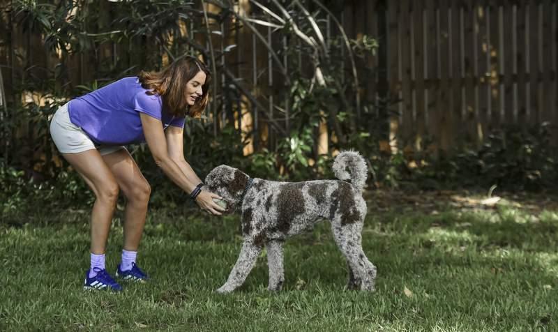 Michele Hall juega con su perro Beau en el jardn de su casa en Bradenton, Florida, el 24 de junio de 2021. Hall, de 54 aos, abogada de profesin, fue diagnosticada con Alzheimer hace unos meses. (AP Foto/Steve Nesius)