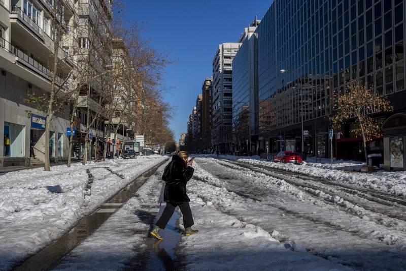 Una mujer cruza una calle nevada en Madrid, Espaa, 11 de junio de 2020. La capital espaola trata de volver a ponerse en marcha tras una nevada rcord que paraliz una gran parte del centro del pas.  (AP Foto/Manu Fernndez)
