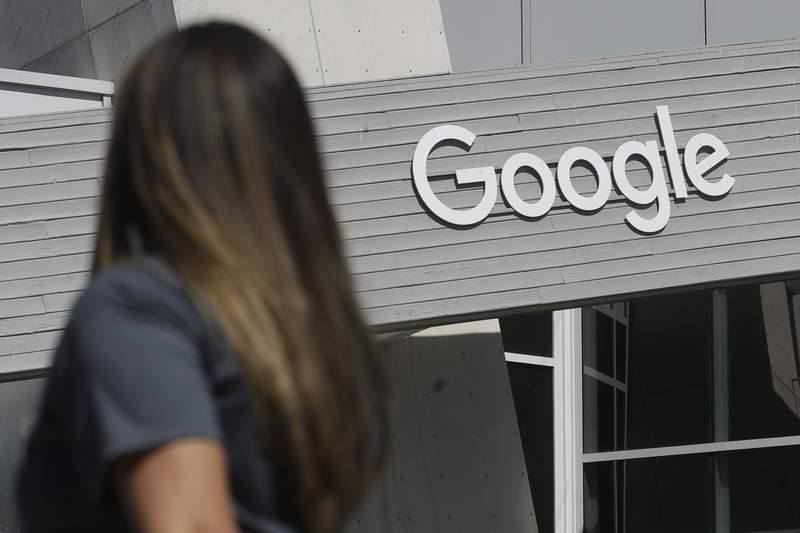 FILE - In this Sept. 24, 2019, file photo a woman walks below a Google sign on the campus in Mountain View, Calif. Australias government said on Tuesday, Feb. 16, 2021, it will amend draft laws that would make Google and Facebook pay for news to clarify that publishers would be paid in lump sums rather than per click on news article links.(AP Photo/Jeff Chiu, File)