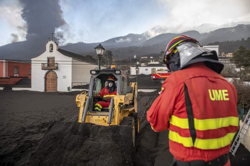 Military Emergency Unit personal clear black ash from volcano as it continues to erupt lava behind a church on the Canary island of La Palma, Spain on Wednesday Oct. 13, 2021. A new lava stream from an erupting volcano threatened to engulf another neighborhood on its way toward the Atlantic Ocean. Island authorities have ordered the evacuation of around 800 people from a section of the coastal town on Tuesday after the lava took a new course and put their homes in its probable path of destruction. (AP Photo/Saul Santos)