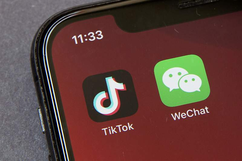 FILE - Icons for the smartphone apps TikTok and WeChat are seen on a smartphone screen in Beijing, in a Friday, Aug. 7, 2020 file photo.  Some U.S.-based users of WeChat are suing President Donald Trump in a bid to block an executive order that they say would effectively prohibit U.S. access to the popular Chinese messaging app. The complaint was filed Friday, Aug. 21, 2020 in San Francisco and asks a federal court judge to stop Trumps order from being enforced. It claims a ban would violate U.S. users constitutional rights.  (AP Photo/Mark Schiefelbein, File)