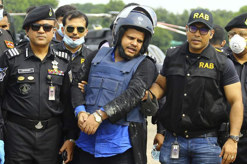 Mohammed Shahed, center, the owner of two hospitals that issued thousands of fake coronavirus test reports is brought by helicopter after being arrested by Bangladesh's Rapid Action Battalion personnel in Dhaka, Bangladesh, Wednesday July 15, 2020. Shahed, a member of the governing party who regularly appeared on TV talk shows, was arrested Wednesday near the Indian border as he attempted to flee the country to India. (AP Photo/Sourav Lasker)