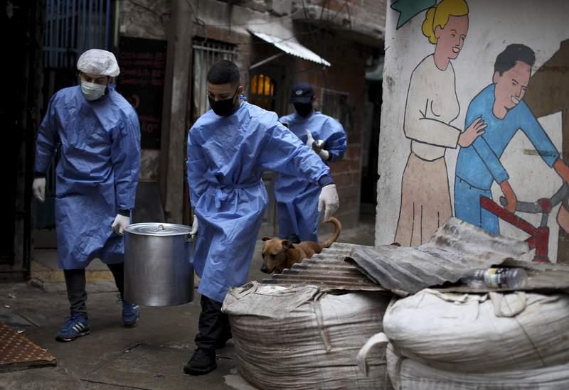 ARCHIVO - En esta foto de archivo del 6 de junio de 2020, voluntarios llevan una olla de comida para los residentes, dentro del barrio marginal de Fraga, durante un cierre ordenado por el gobierno para frenar la propagacin del nuevo coronavirus, en Buenos Aires, Argentina. El gobierno anunci un nuevo paquete de ayuda social el viernes 7 de mayo de 2021, para los sectores ms vulnerables de la poblacin que se han visto afectados por la pandemia y la inflacin. (AP Foto/Natacha Pisarenko, Archivo)