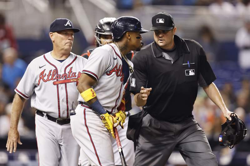 Ronald Acuna Jr. of the Atlanta Braves is held back by umpire Jordan Baker as he attempted to charge the mound after being hit by a pitch from Anthony Bender of the Miami Marlins during the seventh inning at loanDepot park on July 09, 2021 in Miami, Florida.