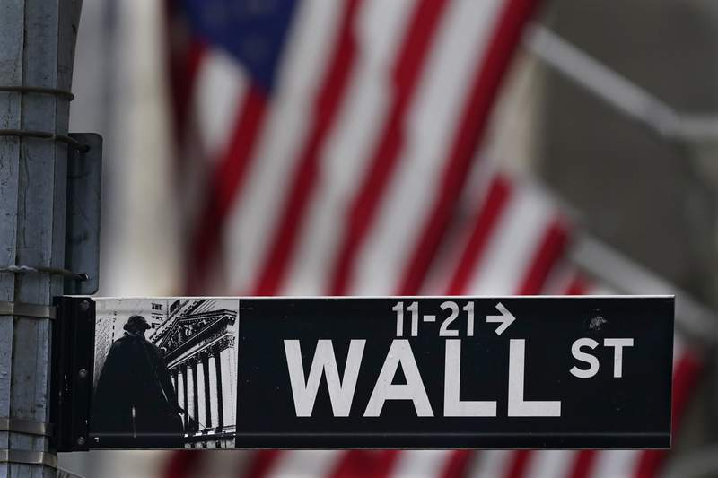 FILE - In this Nov. 23, 2020 file photo, a street sign is displayed at the New York Stock Exchange in New York. Stocks are opening higher on Wall Street after more companies reported strong earnings and as hopes continue to build for another round of help for the economy from Washington. (AP Photo/Seth Wenig, File)