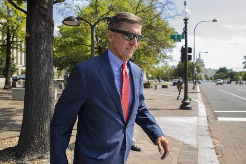 FILE - In this Sept. 10, 2019 file photo, Michael Flynn, President Donald Trump's former national security adviser, leaves the federal court following a status conference in Washington. The arrest of President Donald Trumps former chief strategist Steve Bannon adds to a growing list of Trump associates ensnared in legal trouble. They include the president's former campaign chair, Paul Manafort, whom Bannon replaced, his longtime lawyer, Michael Cohen, and his former national security adviser, Michael Flynn.  (AP Photo/Manuel Balce Ceneta, File)