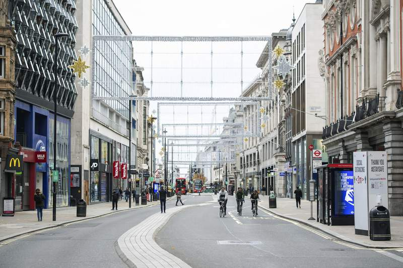 Cyclists ride along a quiet Oxford Street, London, where the majority of shops are closed as England continues a four week national lockdown to curb the spread of coronavirus,  Saturday, Nov. 21, 2020. (Dominic Lipinski/PA via AP)
