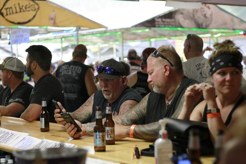 FILE - In this Aug. 7, 2020, file photo, people congregate at One-Eyed Jack's Saloon during the 80th annual Sturgis Motorcycle Rally in Sturgis, S.D. Coronavirus infections in the Dakotas are growing faster than anywhere else in the nation. Infections have been spurred by schools and universities reopening and mass gatherings like the Sturgis Motorcycle Rally, which drew hundreds of thousands of people from across the country. (AP Photo/Stephen Groves, File)