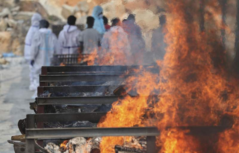 Family members perform last rites of a person who died of COVID-19 as funeral pyres of other victims burn at an open crematorium set up at a granite quarry on the outskirts of Bengaluru, India, Wednesday, May 5, 2021. (AP Photo/Aijaz Rahi)