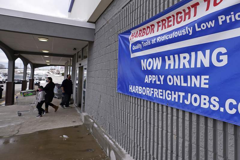 """FILE - In this Dec. 10, 2020, file photo, a """"Now Hiring"""" sign hangs on the front wall of a Harbor Freight Tools store in Manchester, N.H. The latest figures for jobless claims, issued Thursday, Jan. 14, 2021 by the Labor Department, remain at levels never seen until the virus struck.  (AP Photo/Charles Krupa, File)"""