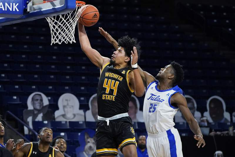 Wichita State forward Isaiah Poor Bear-Chandler (44) reaches for a rebound in front of Tulsa forward Rey Idowu (25) in the second half of an NCAA college basketball game in Tulsa, Okla., Tuesday, Dec. 15, 2020. (AP Photo/Sue Ogrocki)