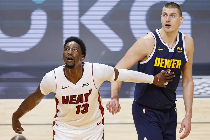 Bam Adebayo of the Miami Heat and Nikola Jokic of the Denver Nuggets look on during the first quarter at American Airlines Arena on January 27, 2021 in Miami, Florida.