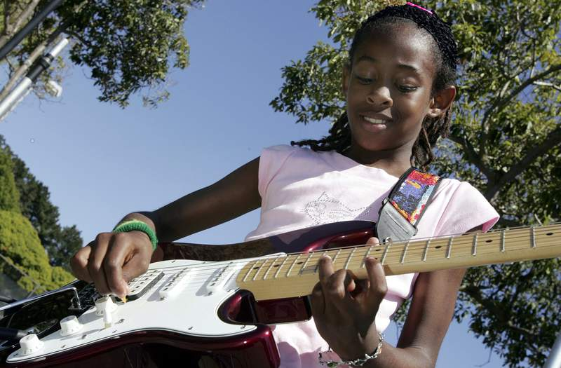 """Ten-year-old Rashida McGee rips through some riffs as her band, """"Visionz of Tomorrow"""" plays at the Juneteenth celebrations at Nichol Park in Richmond, California."""