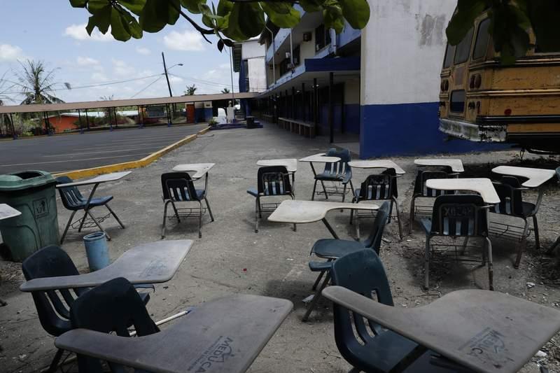 ARCHIVO - En esta fotografa de archivo del 12 de marzo de 2020, los escritorios de los estudiantes estn junto al estacionamiento de la escuela secundaria cerrada Francisco Beckman el primer da que las escuelas cerraron en Panam, en la Ciudad de Panam. Despus de ms de un ao con las escuelas cerradas, algunos estudiantes regresaron a clases parcialmente presenciales el 31 de mayo de 2021. (AP Foto/Arnulfo Franco, Archivo)