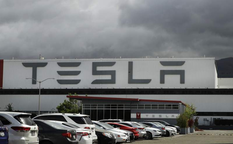 FILE - This Tuesday, May 12, 2020, file photo shows the Tesla plant, in Fremont, Calif. Some Tesla workers and labor activists say the company is threatening to fire employees who havent returned to the companys California factory since it reopened because they're afraid of catching the coronavirus. (AP Photo/Ben Margot, File)