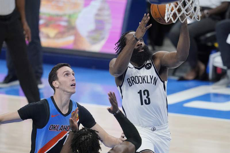 Brooklyn Nets guard James Harden (13) goes to the basket in front of Oklahoma City Thunder forward Aleksej Pokusevski, left, in the second half of an NBA basketball game, Friday, Jan. 29, 2021, in Oklahoma City. (AP Photo/Sue Ogrocki)