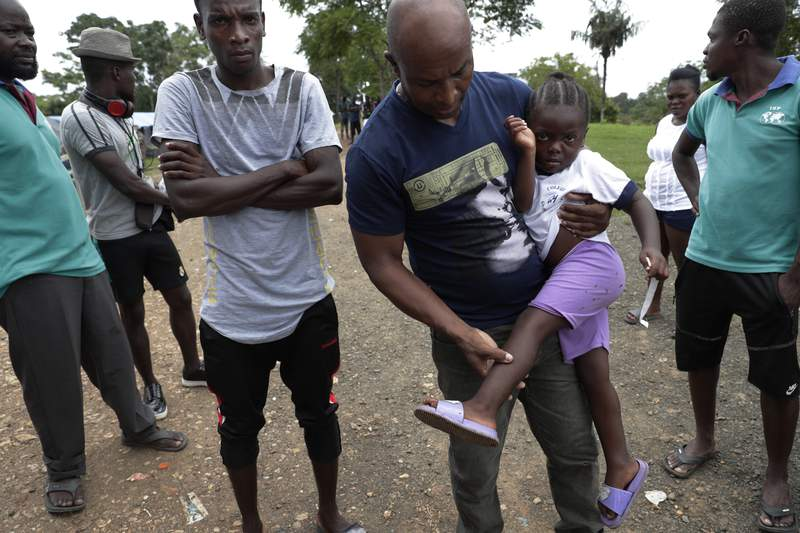 """Haitian migrant Jean Bernadeau show insects bites on a girl's legs, at a migrant camp amid the new coronavirus pandemic in Lajas Blancas, Darien province, Panama, Saturday, Aug. 29, 2020. """"We know there is a strong illness out there. We can't stay here forever."""" Said Bernadeau, a who arrived from Chile after living there for five years and saving $4,000 to continue his journey, """"Here we live like prisoners in a jail."""" He said. (AP Photo/Arnulfo Franco)"""