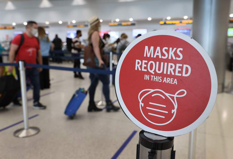 MIAMI, FLORIDA - FEBRUARY 01: A sign reading, 'masks required in this area,' is seen as travelers prepare to check-in for their Delta Airlines flight at the Miami International Airport on February 01, 2021 in Miami, Florida. An executive order signed by U.S. President Joe Biden last week mandates mask-wearing on federal property and on public transportation as part of his plan to combat the coronavirus (COVID-19) pandemic. (Photo by Joe Raedle/Getty Images)