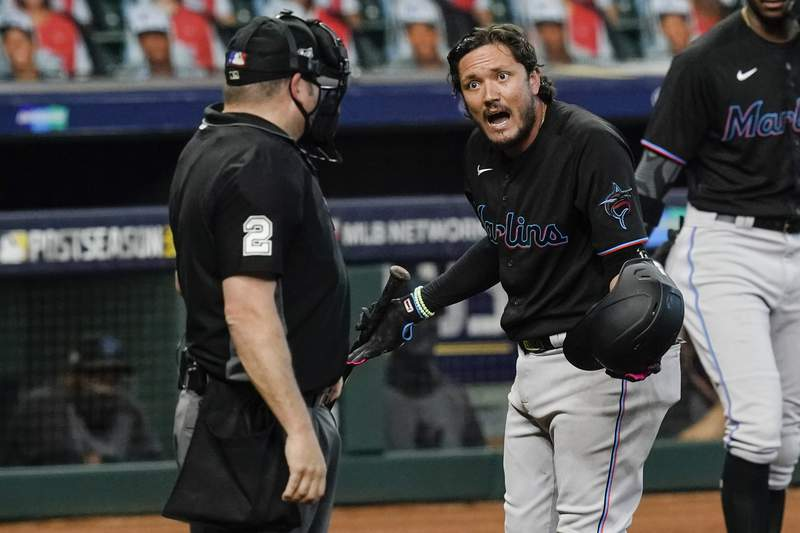 Miami Marlins' Miguel Rojas, right, argues with home plate umpire Dan Bellino after striking out during the seventh inning in Game 2 of a baseball National League Division Series Wednesday, Oct. 7, 2020, in Houston. (AP Photo/Eric Gay)