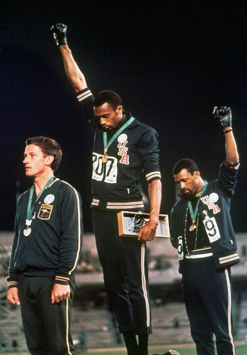 FILE - In this Oct. 16, 1968, file photo, U.S. athletes Tommie Smith, center, and John Carlos extend gloved hands skyward in racial protest during the playing of national anthem after Smith received the gold and Carlos the bronze for the 200 meter run at the Summer Olympic Games in Mexico City. Australian silver medalist Peter Norman is at left. The U.S. Olympic and Paralympic Committee will allow raised fists and kneeling during the national anthem at upcoming Olympic trials. The USOPC released a nine-page document to offer guidance about the sort of racial and social demonstrations that will and won't be allowed by the hundreds of athletes who will compete for spots on the U.S. team in various sports. (AP Photo/File)