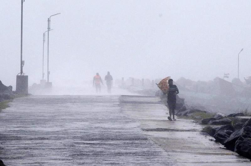 Un hombre intenta sostener su paraguas en el puerto Kasimedu de la costa de Baha de Bengala en Chennai, India, el mircoles 25 de noviembre de 2020. (AP Foto/R. Parthibhan)
