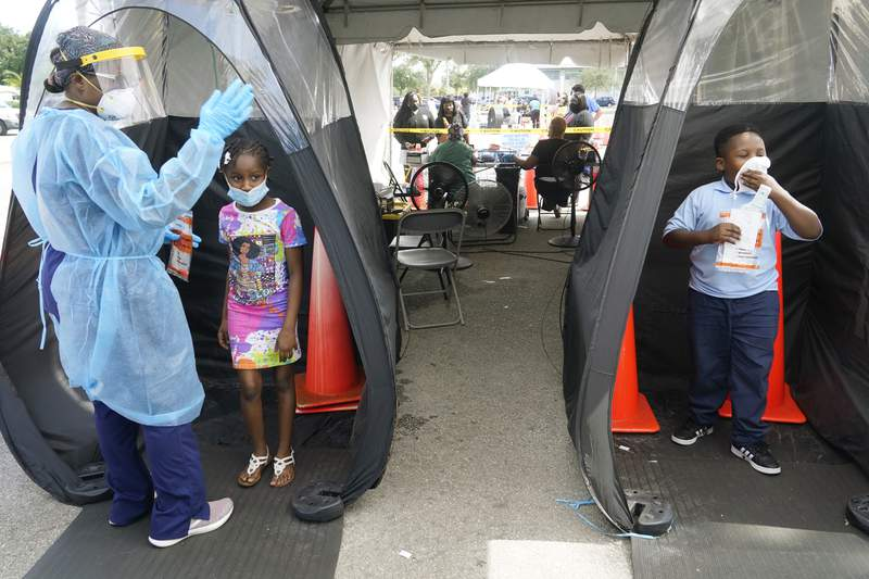 Wenderson Cerisene, 7, right, and his sister Dorah, 9, wait to get tested for COVID-19, Tuesday, Aug. 31, 2021, in North Miami, Fla. Florida schools are seeing a rise in COVID-19 cases forcing of students and teachers to quarantine.