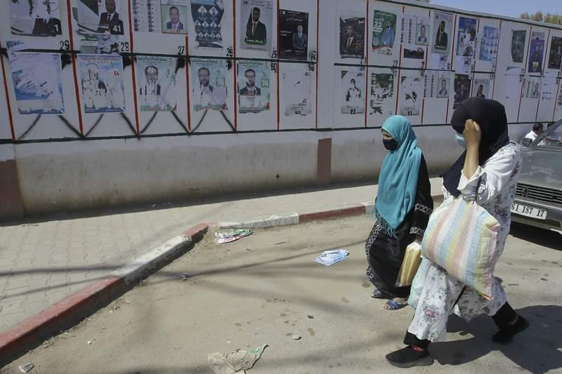 Dos mujeres pasan por delante de un muro con carteles de los candidatos a las elecciones generales, en Ain Ouessara, a 190 kms (118 millas) de Argel, el 10 de junio de 2021. (AP Foto/Fateh Guidoum)