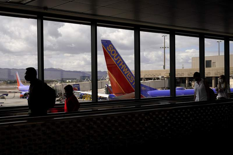 FILE - In this March 26, 2021 file photo, passengers walk past a Southwest Airlines plane at Sky Harbor International Airport in Phoenix. Southwest Airlines is continuing to see higher numbers of canceled and delayed flights as it tries to recover from technology glitches earlier this week. As of Wednesday morning, June 16 the airline had canceled nearly 300 flights and another 400 were delayed, according to tracking service FlightAware.  (AP Photo/Sue Ogrocki, File)