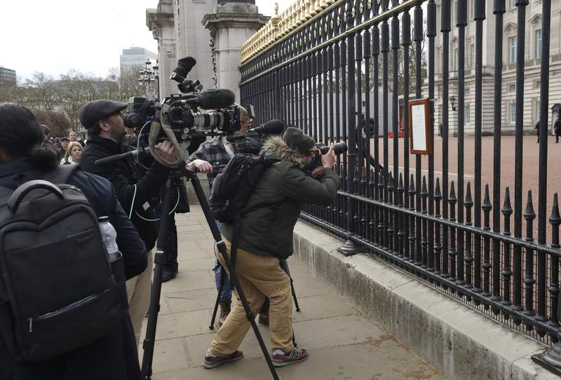 FILE - In this Friday, April 9, 2021 file photo, members of the media take images of an announcement, regarding the death of Britain's Prince Philip, displayed on the fence of Buckingham Palace in London. When Prince Philips death was announced, the BBC switched instantly into mourning mode. Regular programming on the U.K.s national broadcaster was canceled for special coverage, hosted by black-clad news anchors. Some Britons felt it a fitting mark of respect, but for others it was a bit much. (AP Photo/Matt Dunham, File)