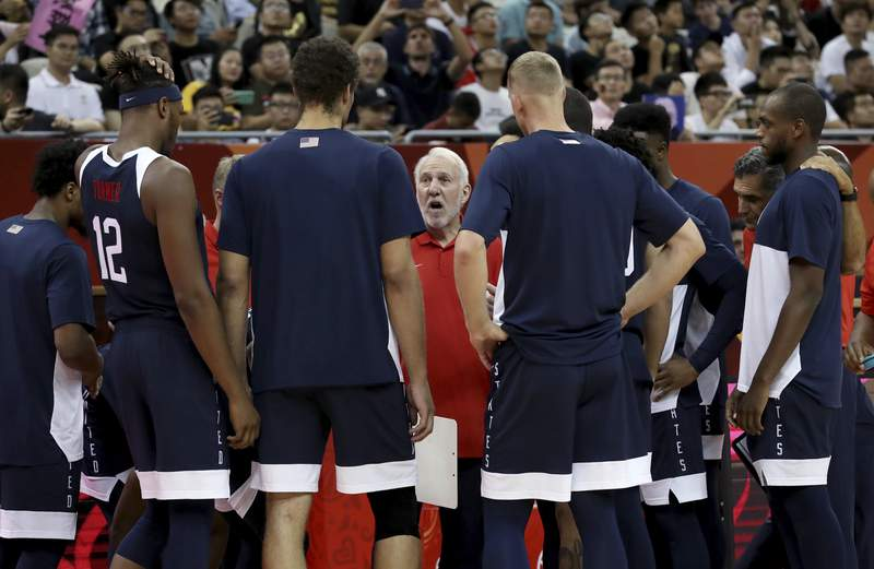 FILE - In this Sept. 1, 2019, file photo, U.S. coach Gregg Popovich talks to players before a Group E match against the Czech Republic in the FIBA Basketball World Cup in Shanghai. Popovich, coach of the San Antonio Spurs, knows that the NBA schedule and how it comes very close to the start of the rescheduled Tokyo Games will be a challenge for USA Basketball to navigate next year when choosing the 12 players who will try to win a fourth consecutive mens Olympic gold medal. Popovich will be head coach of the Olympic team for the first time. (AP Photo/Ng Han Guan, File)