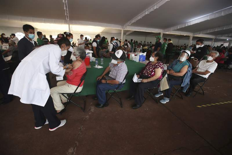Una trabajadora de salud inocula a un hombre con la vacuna AstraZeneca contra el COVID-19 durante una campaa de vacunacin para personas mayores de 60 aos, en el Estadio Olmpico Universitario de la Ciudad de Mxico, el lunes 12 de abril de 2021. Las autoridades mexicanas informaron el viernes que comenzarn la semana prxima el proceso de vacunacin de maestros en cinco estados donde el nivel de contagios es menor con el fin que todos los alumnos puedan volver a clases presenciales antes que termine el ciclo escolar en julio. (Foto AP/Marco Ugarte)