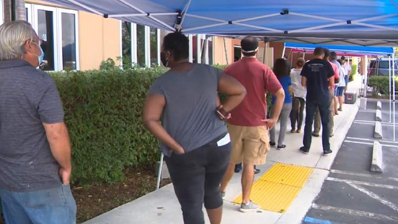 People wait in line outside the Allen Park Community Center vaccination site in North Miami Beach.