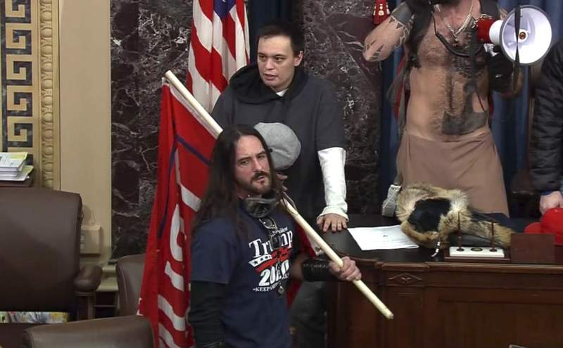FILE - In this file image from U.S. Capitol Police video, Paul Allard Hodgkins, 38, of Tampa, Fla., front, stands in the well on the floor of the U.S. Senate on Jan. 6, 2021, at the Capitol in Washington. (U.S. Capitol Police via AP, File)