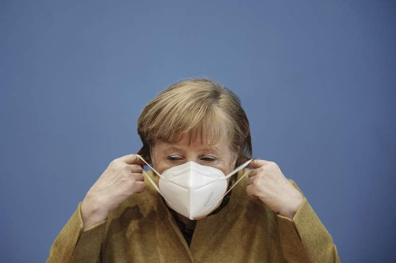 German Chancellor Angela Merkel arrives wearing a protective mask for a press conference on the current situation in Berlin, Germany, Thursday, Jan. 21, 2021. Topics include the decisions taken by the federal and state governments to combat the Corona pandemic, the Chancellor's upcoming virtual consultations with the heads of state and government of the European Union (EU), and relations with the United States following the inauguration of the new president. (Michael Kappeler/Pool via AP)