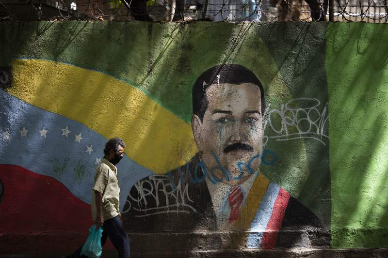 A man wearing a face mask amid the COVID-19 pandemic passes a mural of Venezuelan President Nicolas Maduro in Caracas, Venezuela, Wednesday, July 22, 2020. Analysts say that in recent months the pandemic has helped suck away the oppositions scanty momentum and bolster Maduros already strong hand. (AP Photo/Ariana Cubillos)