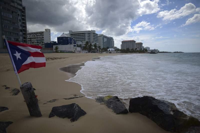 ARCHIVO - En esta fotografa del 21 de mayo de 2020 se muestra una bandera de Puerto Rico en una playa vaca en San Juan, Puerto Rico. (AP Foto/Carlos Giusti, Archivo) PUERTO RICO OUT-NO PUBLICAR EN PUERTO RICO