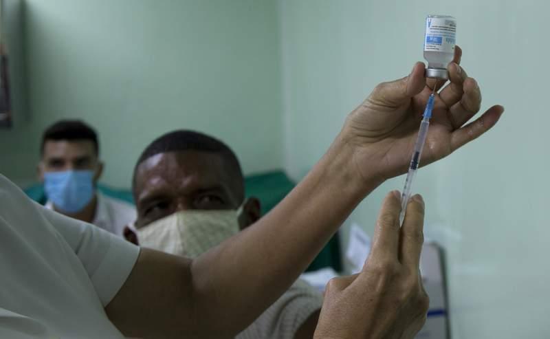 Eusebio Torres espera ser vacunado mientras una enfermera prepara la dosis de la vacuna cubana Abdala para el COVID-19 en el hospital Gustavo Aldereguia de Cienfuegos, Cuba, el domingo 30 de mayo de 2021. (AP Foto/Ismael Francisco)