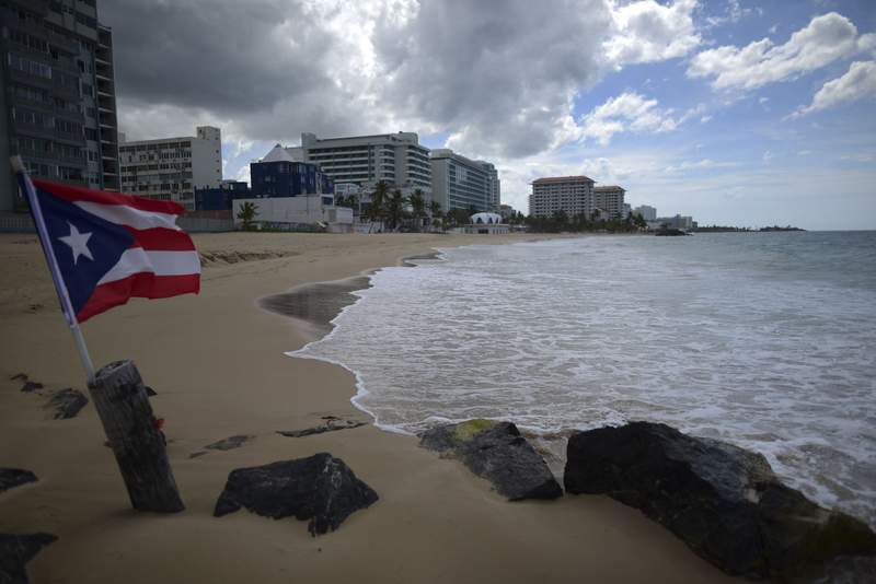 FILE - In this May 21, 2020 file photo, a Puerto Rican flag flies on an empty beach at Ocean Park, in San Juan, Puerto Rico. Puerto Ricos governor announced Thursday, June 11, that she will lift nearly all restrictions aimed at curbing coronavirus cases, which means beaches, churches and businesses including movie theaters and gyms across the U.S. territory will reopen after three months. (AP Photo/Carlos Giusti, File) PUERTO RICO OUT-NO PUBLICAR EN PUERTO RICO