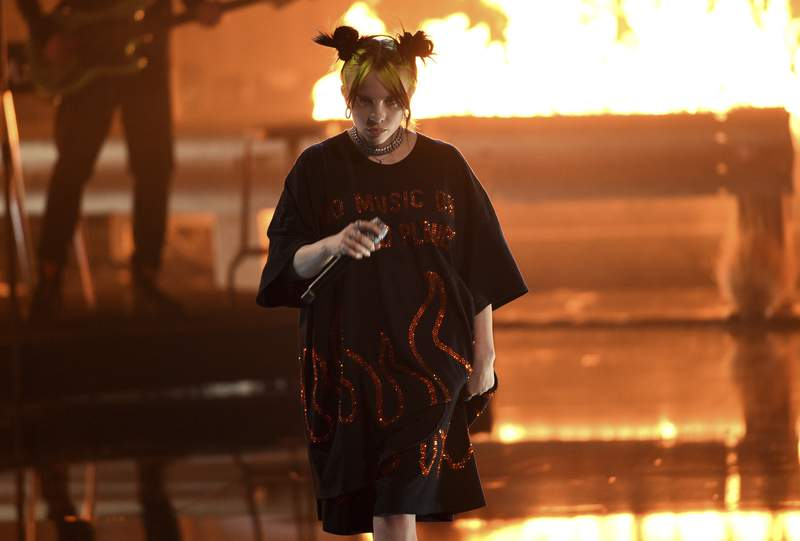 """FILE - In this Sunday, Nov. 24, 2019, file photo, Billie Eilish performs """"all the good girls go to hell,"""" at the American Music Awards at the Microsoft Theater in Los Angeles. iHeartMedia announced Wednesday, Jan. 8, 2020, that Eilish received seven nominations, as the singer will compete for female artist of the year and song of the year with bad guy. Lil Nas X and Lizzo are each nominated six times. (Photo by Chris Pizzello/Invision/AP, File)"""
