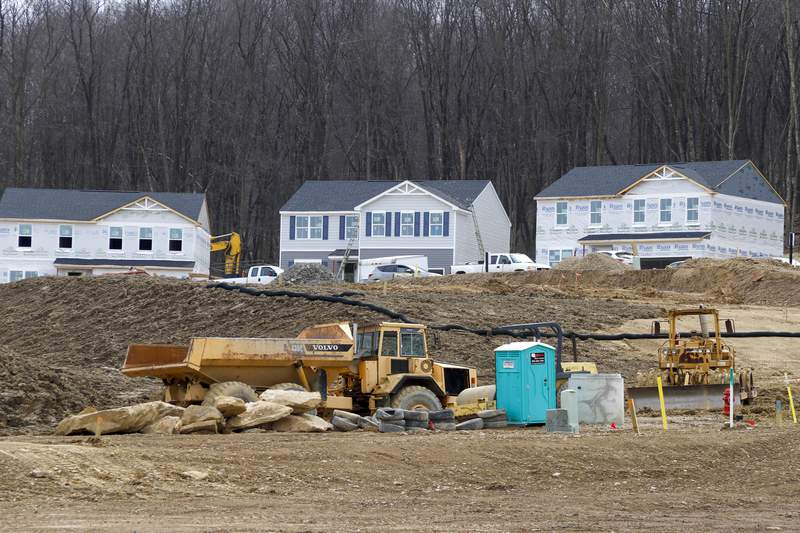 In this March 18, 2020 photo, Construction continues at a housing plan in Zelienople, Pa.,  The housing market has stalled, but homebuilder stocks are up sharply amid signs that sales are starting to improve. Still, the outlook for a housing market recovery remains cloudy, given uncertainty over the pandemic's impact. (AP Photo/Keith Srakocic)