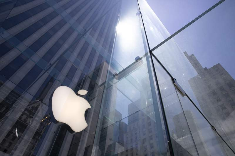 FILE - In this June 16, 2020 file photo, the sun is reflected on Apple's Fifth Avenue store in New York. Apple is the first U.S. company to boast a market value of $2 trillion, just two years after it became the first to reach $1 trillion. Apple shares have gained nearly 60% this year as the company overcame the shutdown of factories in China that produce the iPhone and the closure of its retail sales amid the coronavirus pandemic.  (AP Photo/Mark Lennihan, File)