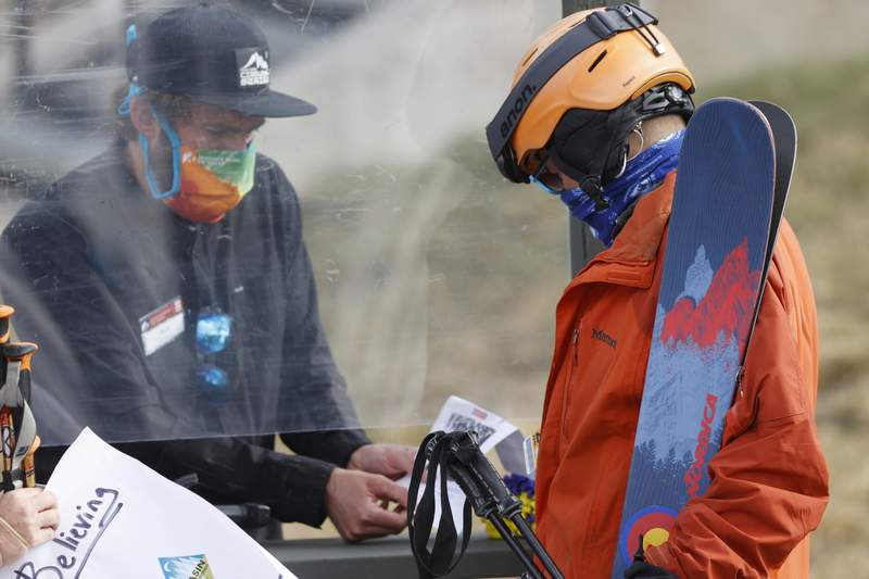 An employee is protected by a plexiglass shield while processing a skier at the reopening of Arapahoe Basin Ski Resort, which closed in mid-March to help in the effort to stop the spread of the new coronavirus, in a Wednesday, May 27, 2020 file photo, in Keystone, Colo. An executive order signed y President Donald Trump that temporarily bans a wide variety of foreign visas has thrown another obstacle in the path of ski resorts as they try to hire enough temporary workers to fill crucial jobs in the era of COVID-19. (AP Photo/David Zalubowski, File)