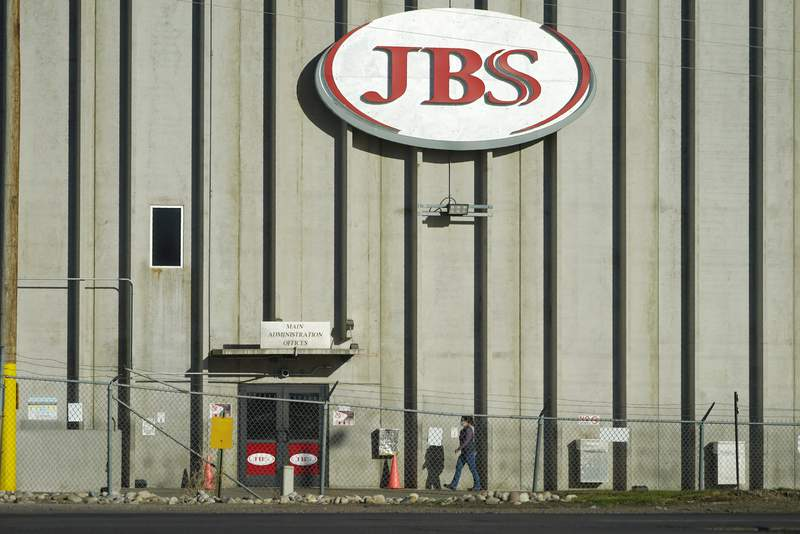 FILE - In this Oct. 12, 2020 file photo, a worker heads into the JBS meatpacking plant in Greeley, Colo. Meatpacker JBS Foods Inc. faces about $59,000 in fines after a worker fell into vat of chemicals used to process animal hides and died at one of the company's meat processing facilities in northern Colorado, officials said. (AP Photo/David Zalubowski, File)